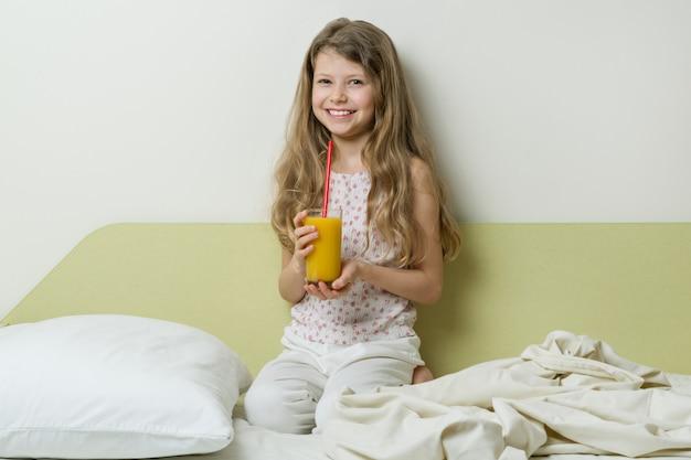 Menina com sono de pijama senta-se na cama em casa