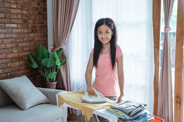 Menina com sorriso segurando o ferro e passando roupas em uma tábua de passar em um quarto em casa