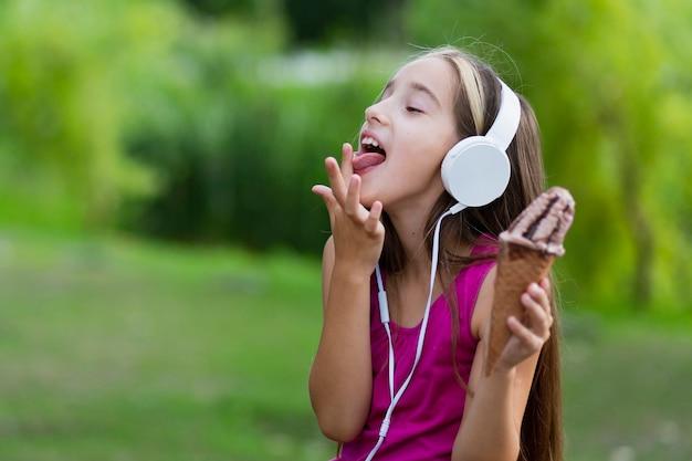 Menina com sorvete lambendo os dedos