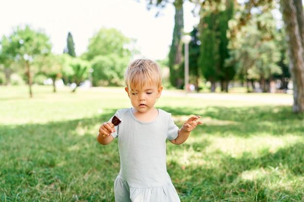 Menina com sorvete na mão fica em um gramado verde
