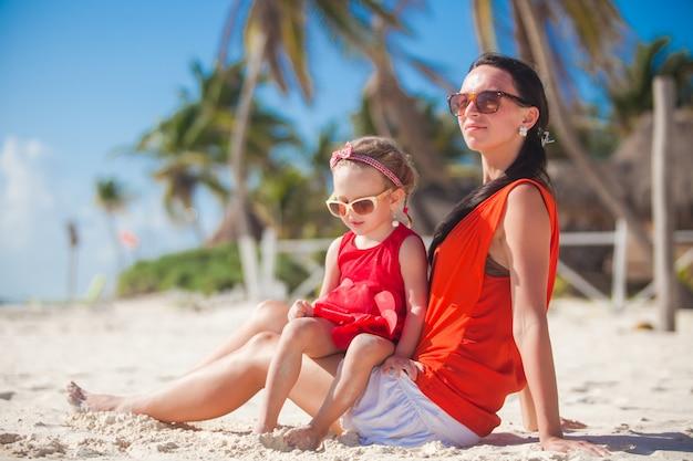 Menina com sua jovem mãe relaxando na praia das caraíbas