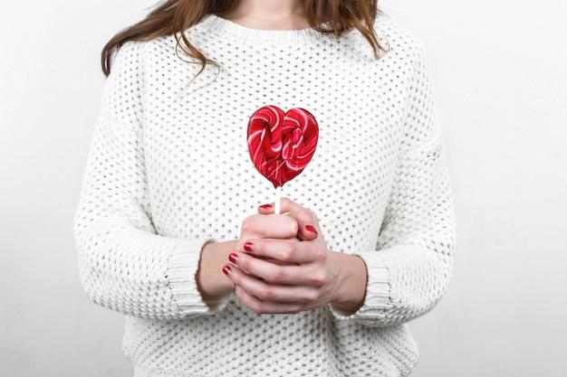 Menina com suéter branco segurando em mãos lollipop saboroso e doce em t