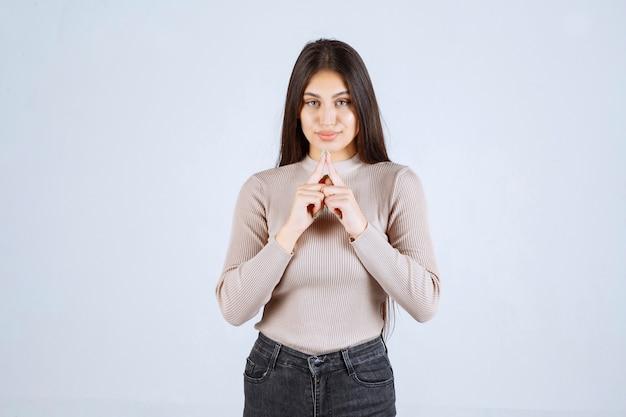 Menina com suéter cinza dando poses desagradáveis e sedutoras.