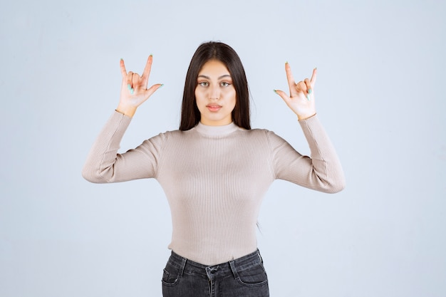 Menina com suéter cinza fazendo sinal de lobo.