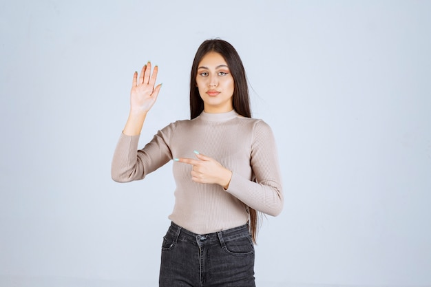 Menina com suéter cinza, levantando as mãos.