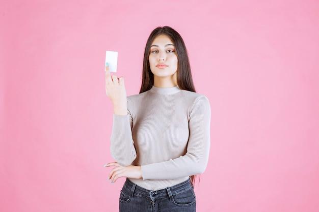Menina com suéter cinza mostrando e apresentando seu cartão de visita
