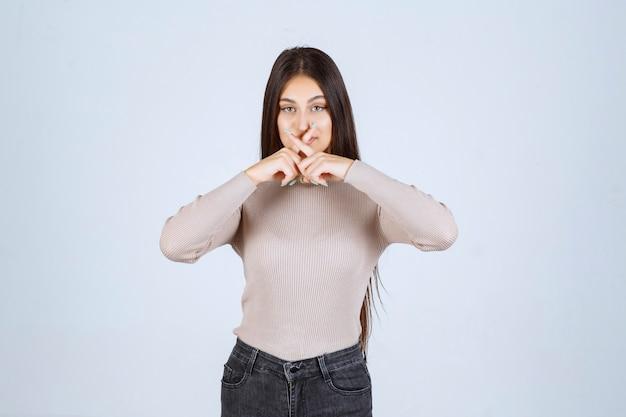 Menina com suéter cinza sente o cheiro ruim e cobre o nariz.