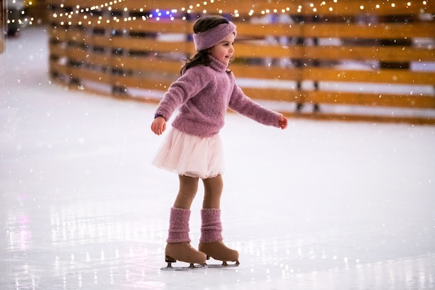 Menina com suéter rosa patina em uma noite de inverno com neve em uma pista de gelo ao ar livre