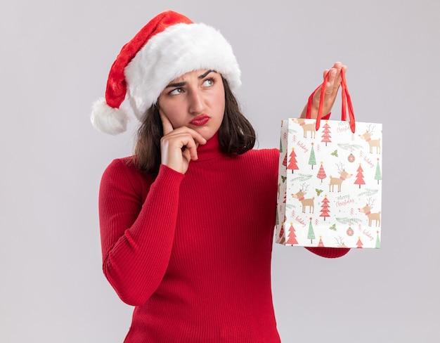 Menina com suéter vermelho e chapéu de papai noel segurando um saco de papel colorido com presentes de natal olhando de lado com expressão cética pensando em pé sobre um fundo branco