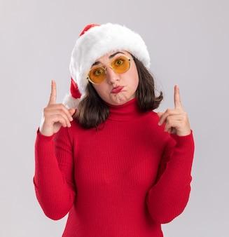 Menina com suéter vermelho e chapéu de papai noel usando óculos, olhando para a câmera com uma expressão triste mostrando os dedos indicadores franzindo os lábios em pé sobre um fundo branco