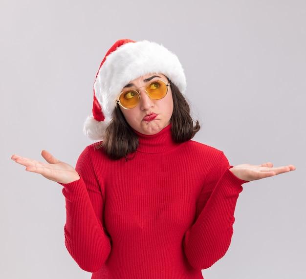 Menina com suéter vermelho e chapéu de papai noel usando óculos, parecendo confusa, espalhando os braços para os lados em pé sobre um fundo branco