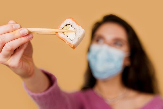 Menina com sushi em máscara médica em fundo amarelo