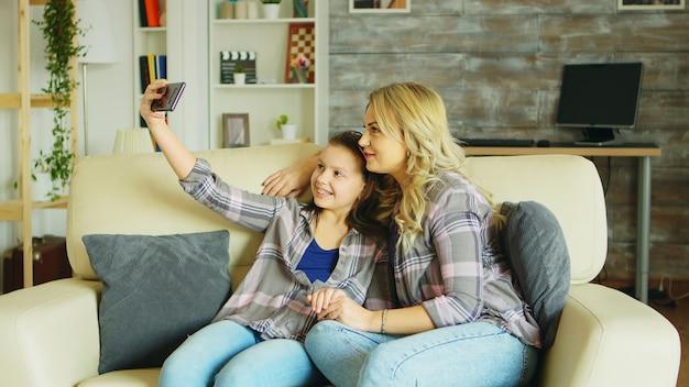 Menina com suspensórios, sentada no sofá da sala, tirando uma selfie com a mãe.