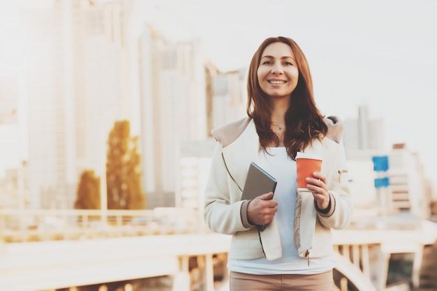 Menina com tablet com edifícios no fundo.