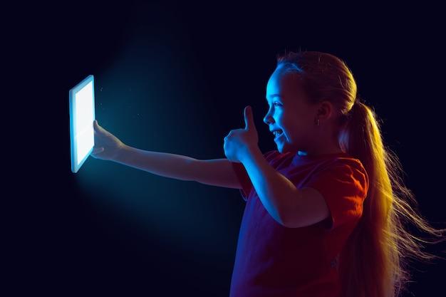 Menina com tablet em luz neon