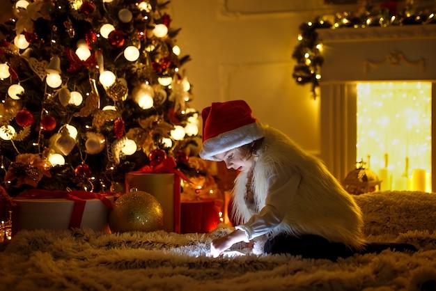Menina com tablet perto de árvore de natal