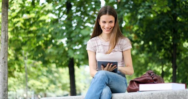 Menina com tablet sentado num banco do parque