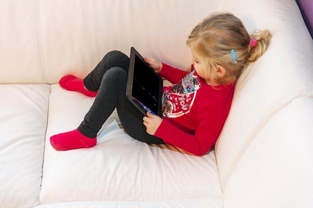 Menina, com, tabuleta, sentar sofá