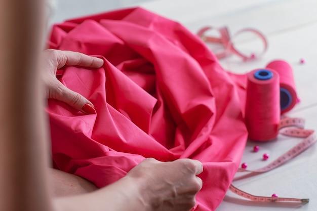 Menina com tecido de cetim rosa com fios e centímetros em fundo de madeira com miçangas.