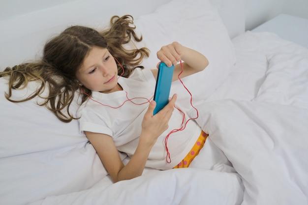 Menina com telefone celular em fones de ouvido, sentado na cama branca em casa