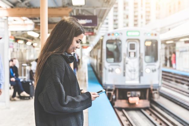 Menina com telefone inteligente na estação de trem em chicago