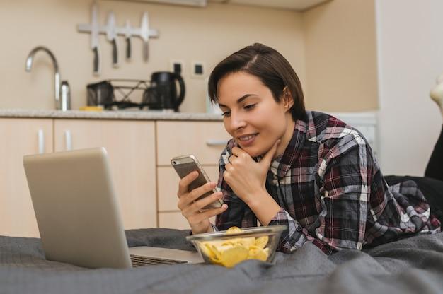 Menina com telefone na cama, comendo batatas fritas