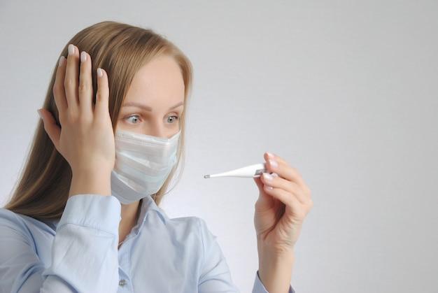 Menina com termômetro e máscara médica