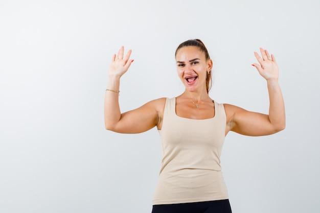 Menina com top bege, calça preta levantando as palmas das mãos em gesto de rendição
