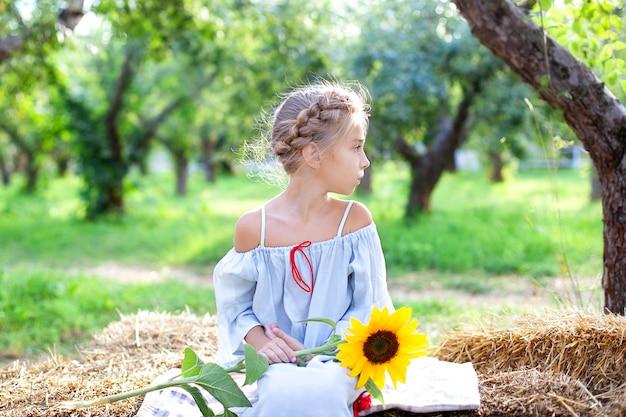 Menina com trança na cabeça dela senta-se no rolo de palheiros no jardim e detém girassol. criança senta-se na palha e gosta de natureza na zona rural.