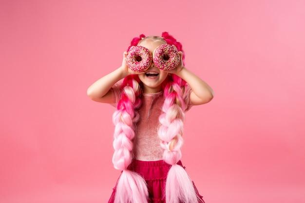 Menina com tranças kanekalon com donuts em fundo rosa