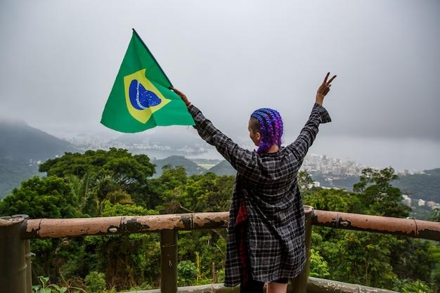 Menina com tranças roxas na cabeça acenando uma bandeira brasileira.