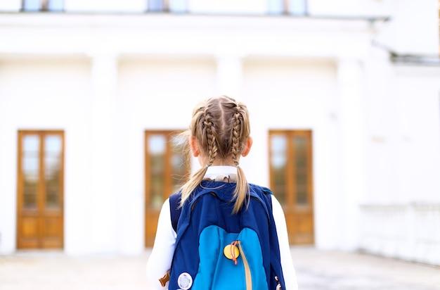Menina com tranças trançadas em uniforme de vestido vai para a escola com mochila azul