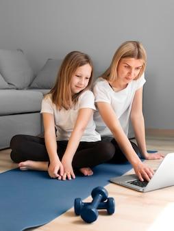 Menina com treino de desporto mãe com pesos após vídeos