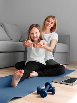 Menina com treino de desporto mãe com pesos