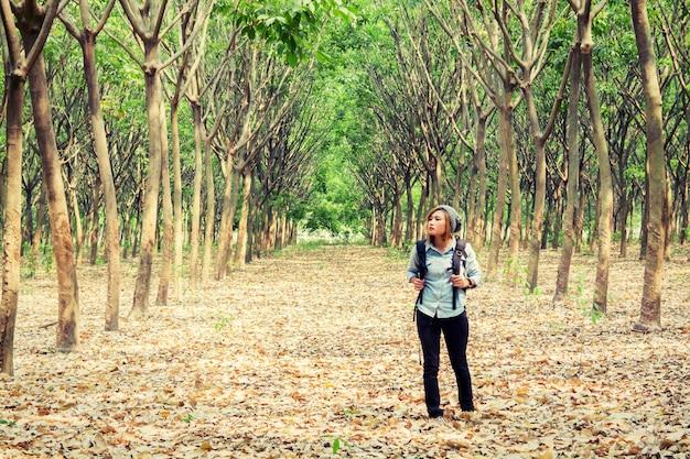 Menina com trouxa observando as árvores