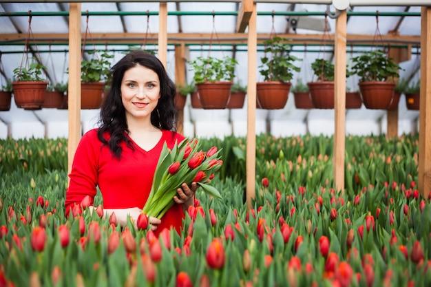 Menina com tulipas crescidas em uma estufa.