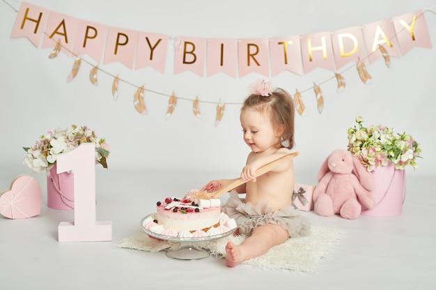 Menina com um bolo de aniversário, sessão de fotos de bebê de 1 ano