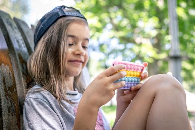 Menina com um boné com um smartphone em um estojo no estilo de brinquedos anti-stress estourá-lo.