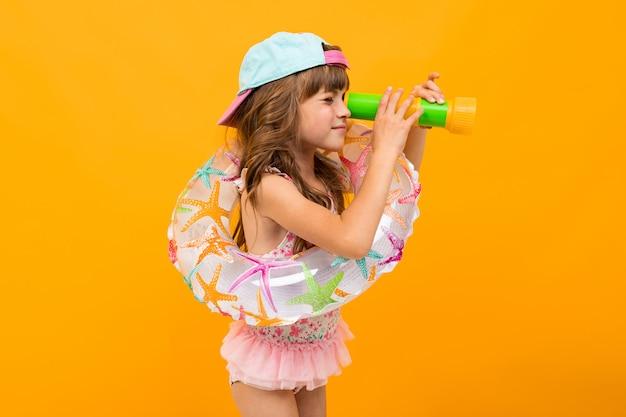 Menina com um boné de beisebol em um maiô com um círculo de natação em uma parede amarela