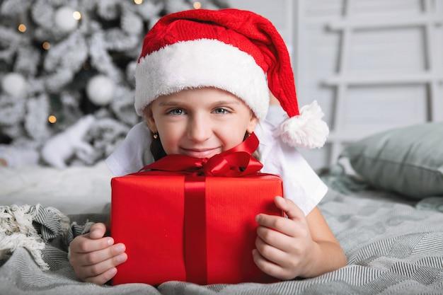 Menina com um boné vermelho com um presente de natal. ela deita na cama, abraça a caixa contra o fundo da árvore de natal.
