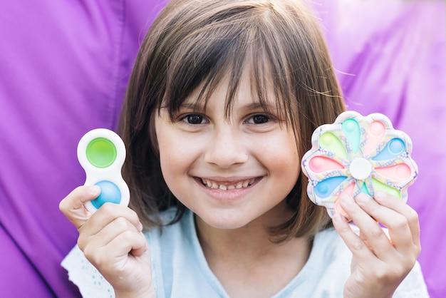 Menina com um brinquedo popit moderno colorido e brilhante pop it brinquedo covinha simples