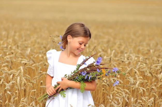 Menina com um buquê de flores silvestres nas mãos em um campo de trigo.