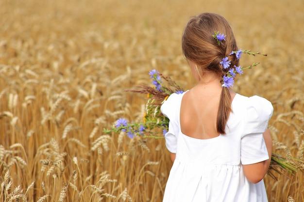 Menina com um buquê de flores silvestres no campo