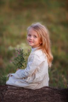 Menina com um buquê de flores silvestres