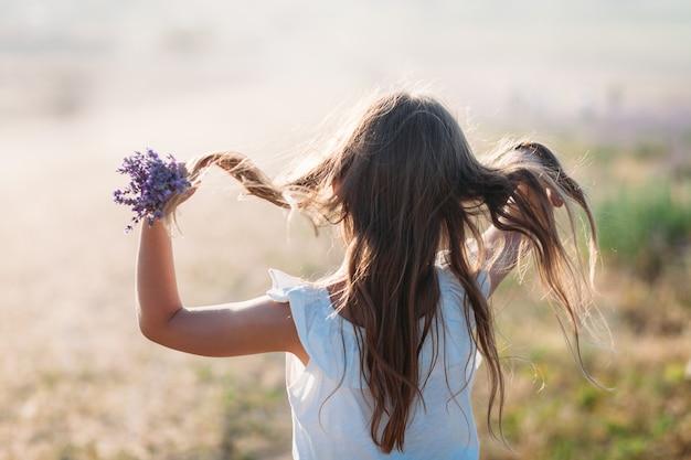 Menina com um buquê de lavanda alisa o cabelo na parte de trás