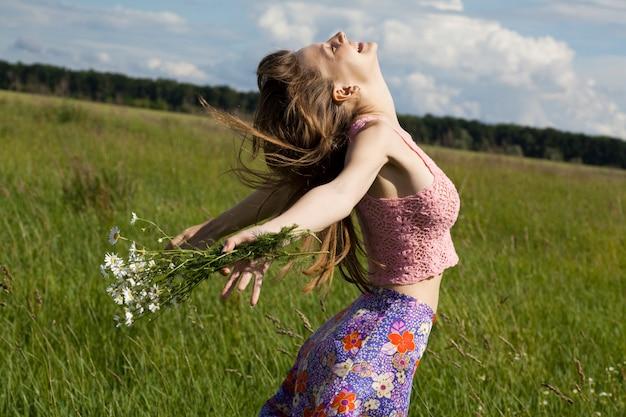 Menina com um buquê de margaridas em um campo