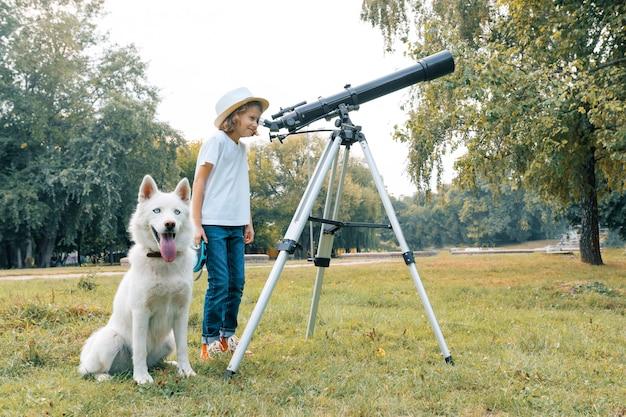 Menina com um cachorro branco, olhando através de um telescópio para o céu