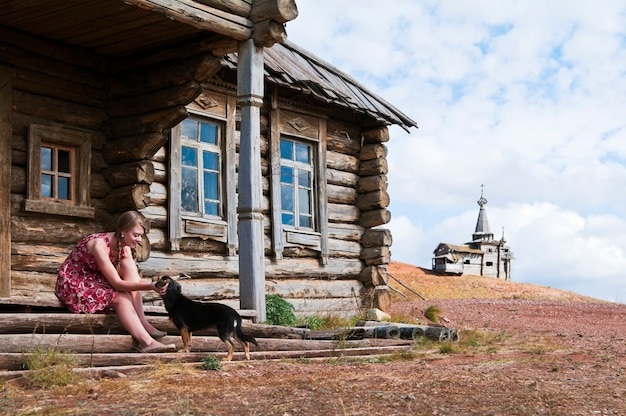 Menina com um cachorro na porta de uma velha casa de madeira