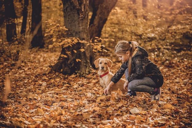 Menina com um cachorro no parque