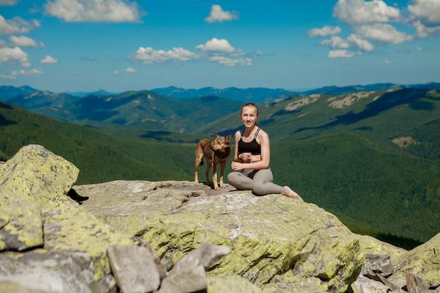 Menina com um cachorro no topo de uma montanha, assistindo a uma bela paisagem com os braços bem abertos